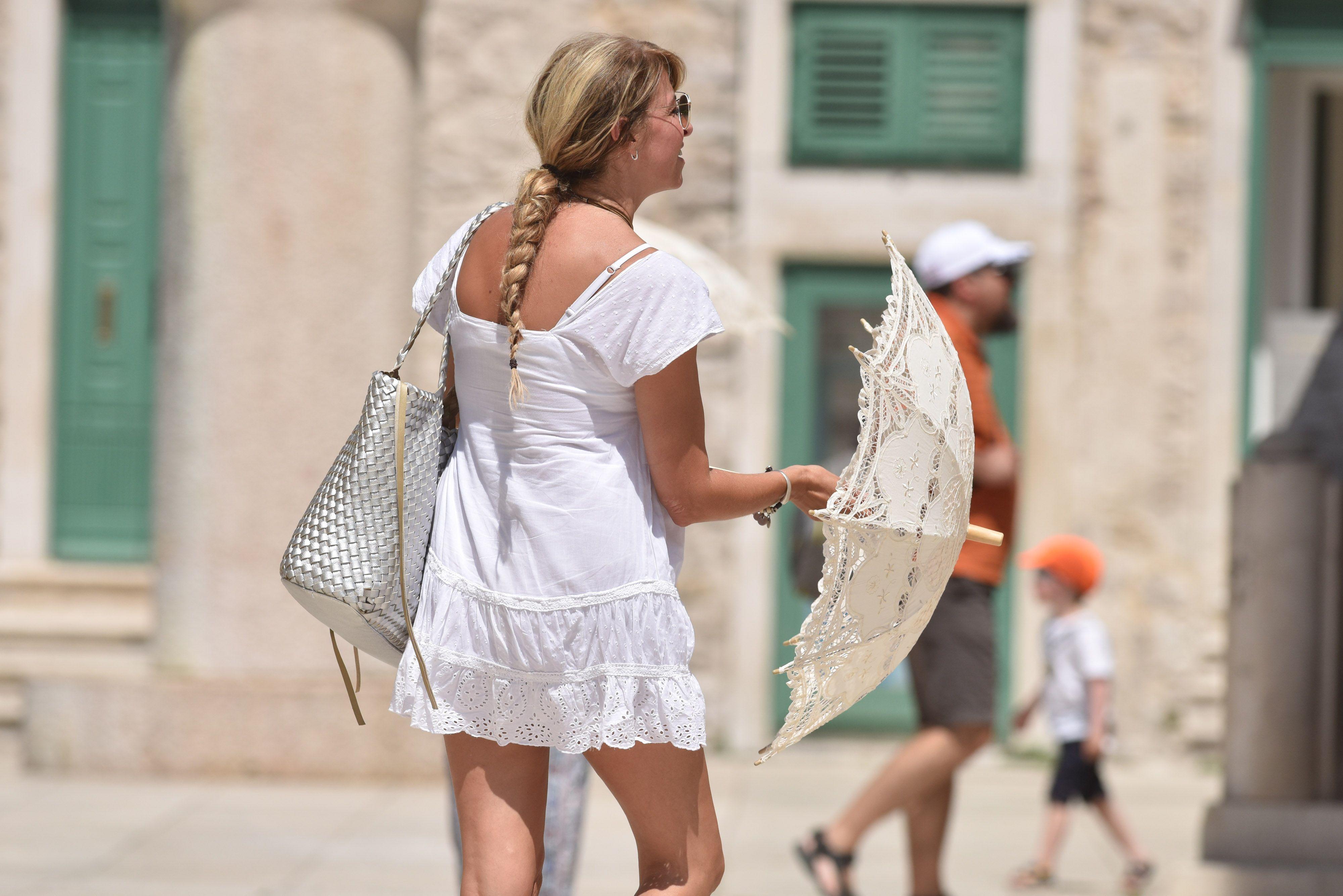 U bijeloj haljinici i sa suncobranom plijenila je pozornost na ulicama Šibenika